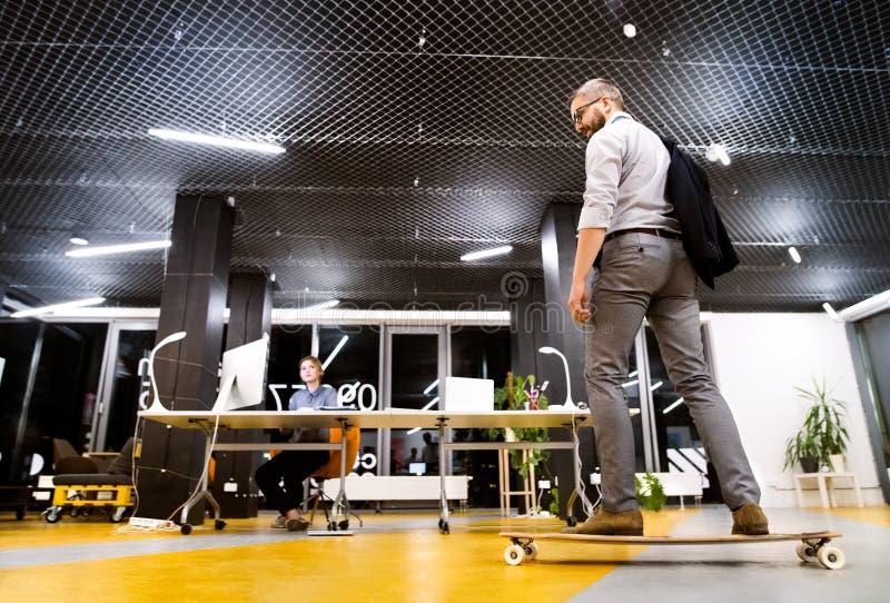 Hommes d'affaires dans le bureau la nuit fonctionnant tard images libres de droits