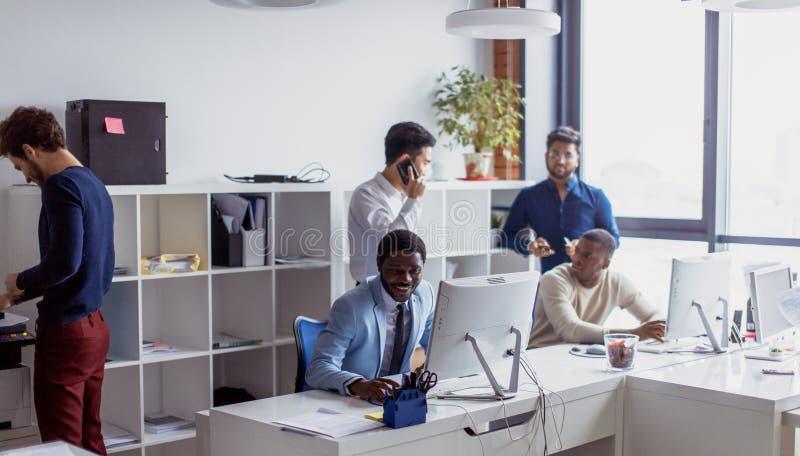Hommes d'affaires dans un bureau de l'espace ouvert avec une fenêtre panoramique, possibilité éloignée photo stock