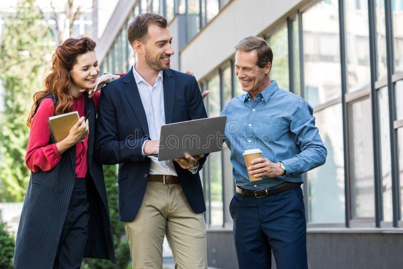 hommes d'affaires de sourire avec du café à aller et le fonctionnement de journal intime ensemble image libre de droits