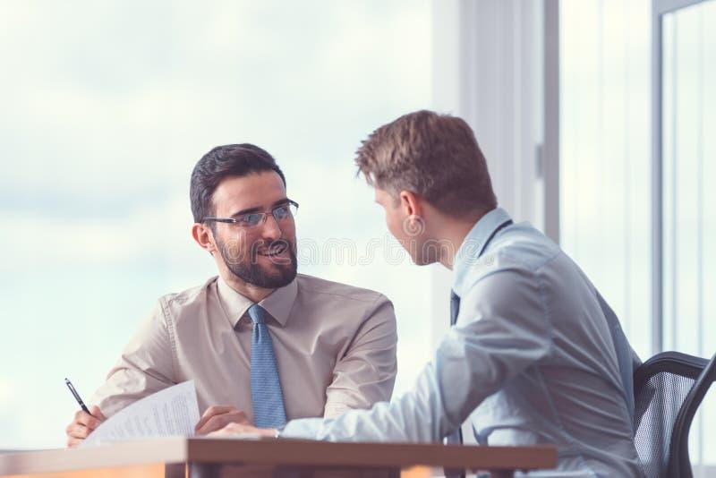 Hommes d'affaires de sourire lors de la réunion photo libre de droits