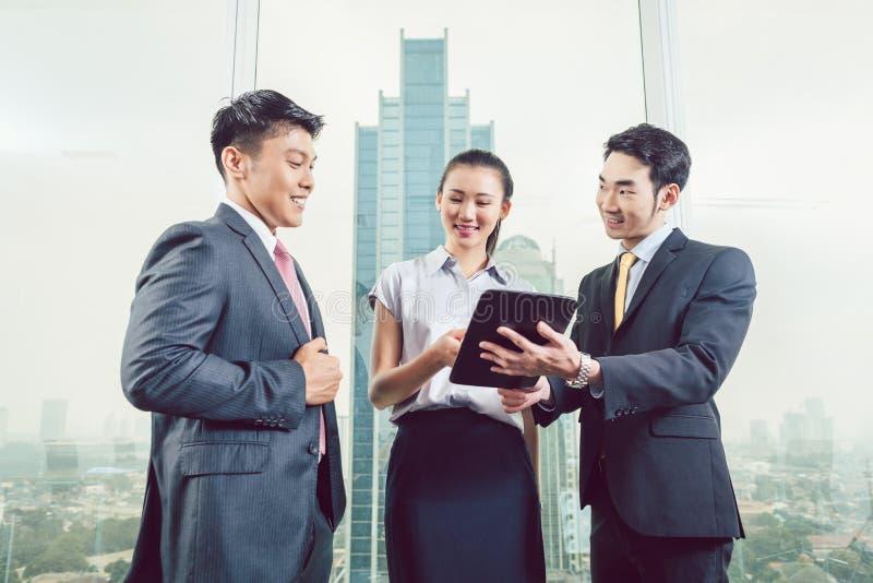 Hommes d'affaires de sourire regardant le comprimé numérique photos stock