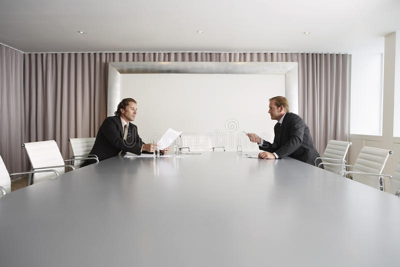 Hommes d'affaires discutant dans la salle de conférence image stock
