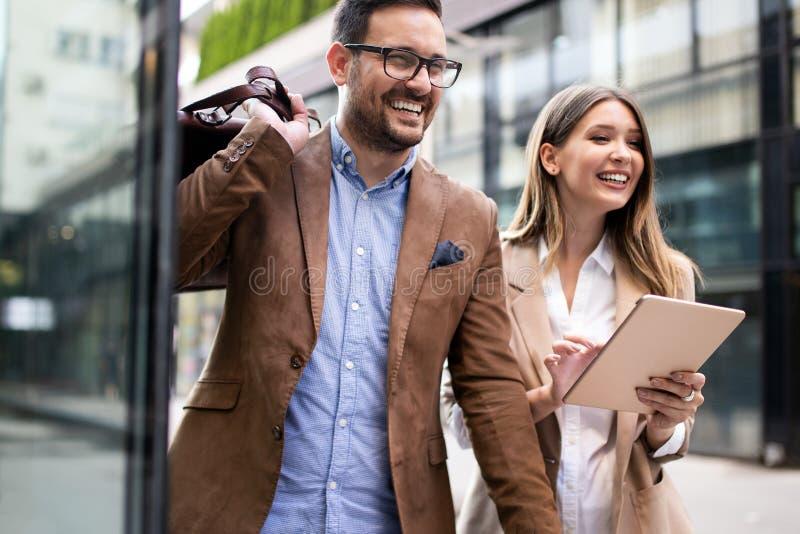 Hommes d'affaires discutant et souriant tout en marchant ensemble extérieur photos stock