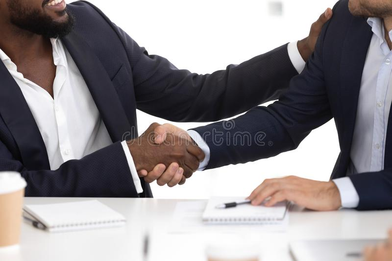 Hommes d'affaires divers de plan rapproché dans les costumes se saluant avec la poignée de main image stock