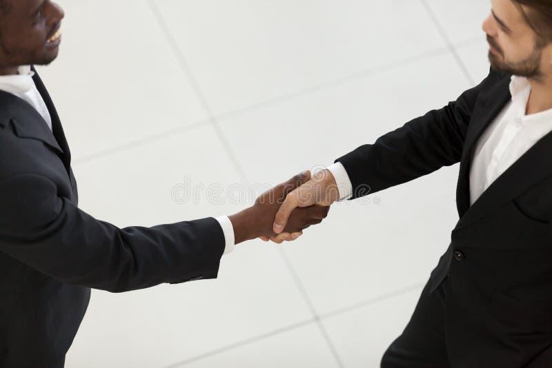 Hommes d'affaires divers de vue de côté dans les costumes se serrant la main images stock