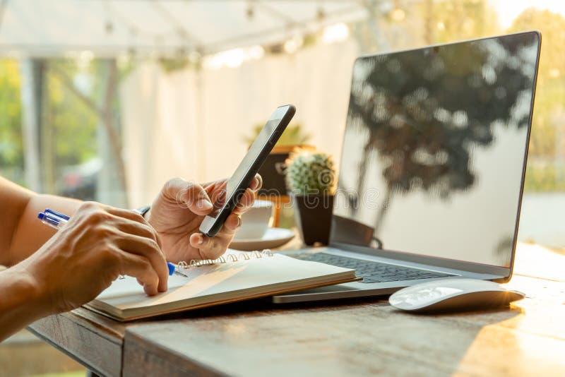 Hommes d'affaires employant des téléphones portables et l'écriture sur le carnet avec le stylo sur la table images stock
