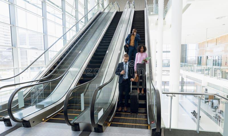Hommes d'affaires en voyage divers descendant un escalator images stock