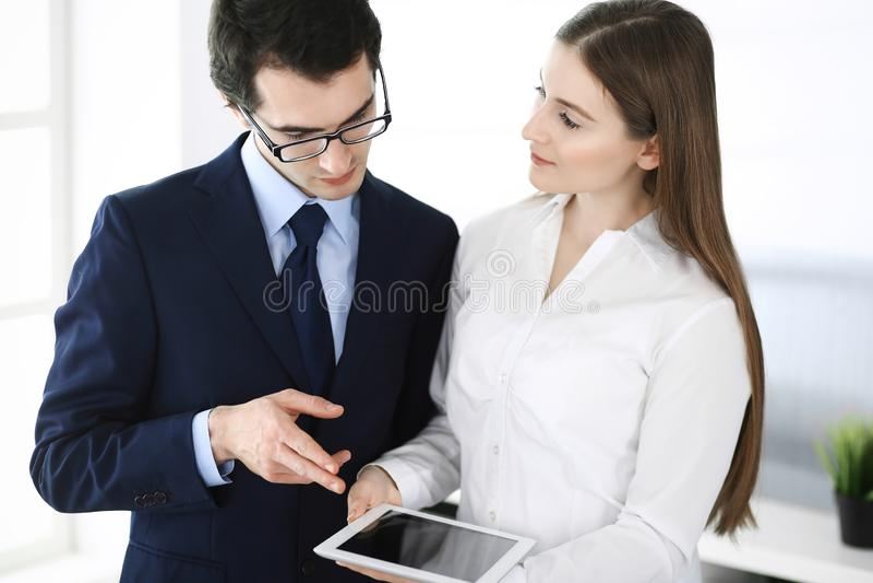 Hommes d'affaires et femme ? l'aide de la tablette dans le bureau moderne Coll?gues ou chefs d'entreprise sur le lieu de travail  image stock