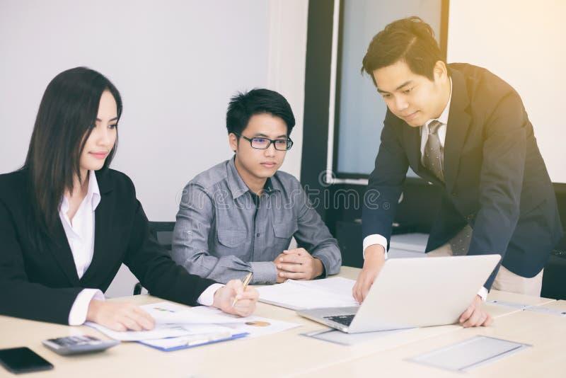 Hommes d'affaires et groupe asiatiques utilisant le carnet pour des associés photo libre de droits
