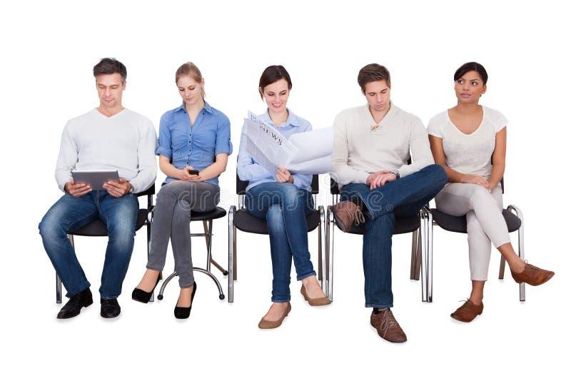 Hommes d'affaires faisant de diverses activités sur des chaises image libre de droits