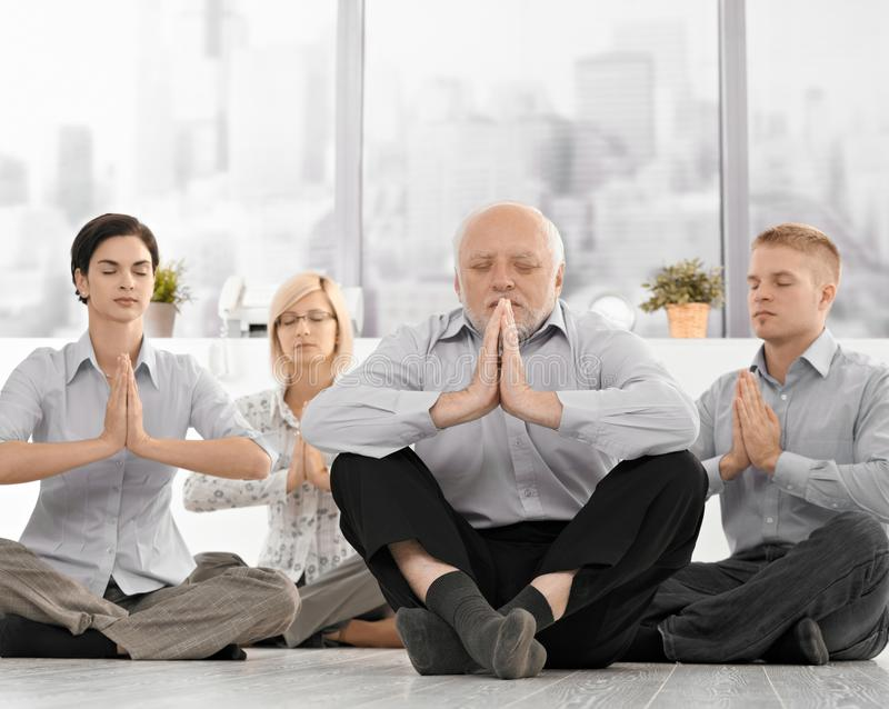 Hommes d'affaires faisant la méditation dans le bureau images libres de droits