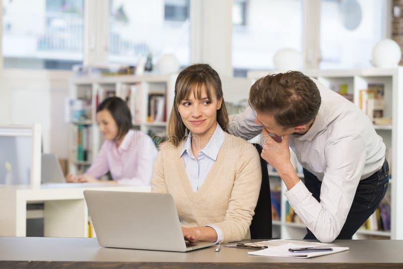 Hommes d'affaires flirtant au travail dans le bureau photos libres de droits