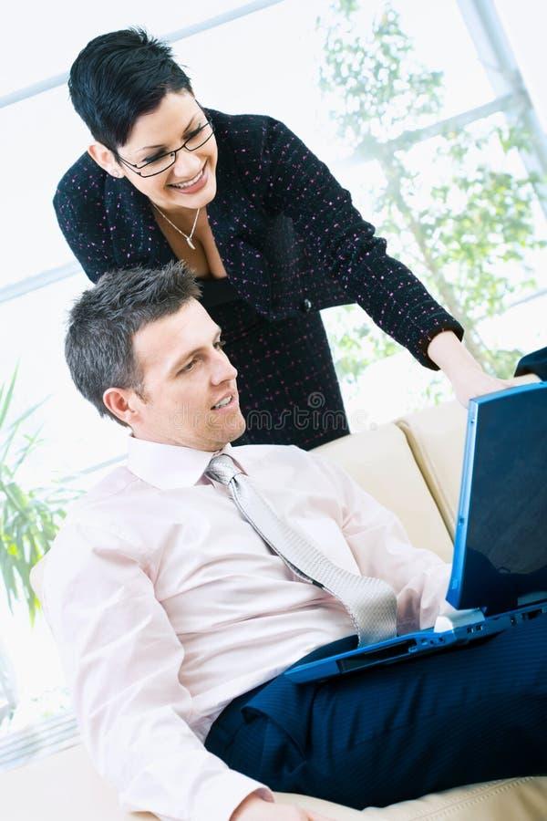 Hommes d'affaires heureux avec l'ordinateur photographie stock