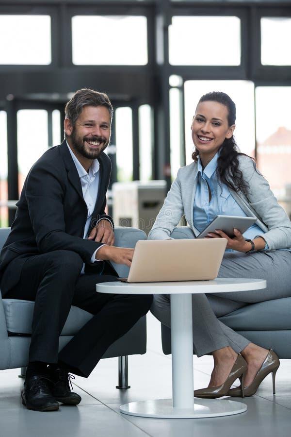 Hommes d'affaires heureux s'asseyant avec l'ordinateur portable images libres de droits