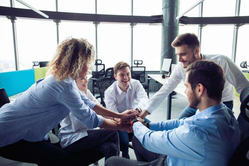 Hommes d'affaires mettant leurs mains sur l'un l'autre dans le poste de travail léger agréable, vêtements sport de port Conceptio image stock
