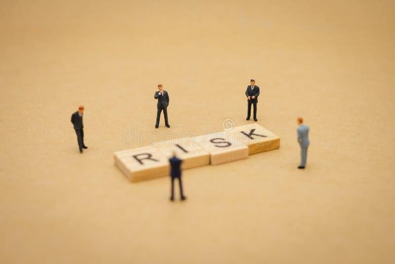 Hommes d'affaires miniatures de personnes se tenant avec le mot en bois RISQUE employant en tant que le concept d'affaires de fon photographie stock libre de droits