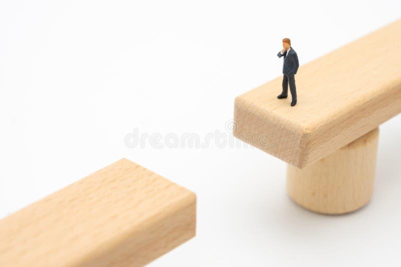 Hommes d'affaires miniatures de personnes se tenant sur un pont en bois regardant le bord opposé, analysant la manière d'atteindr photographie stock