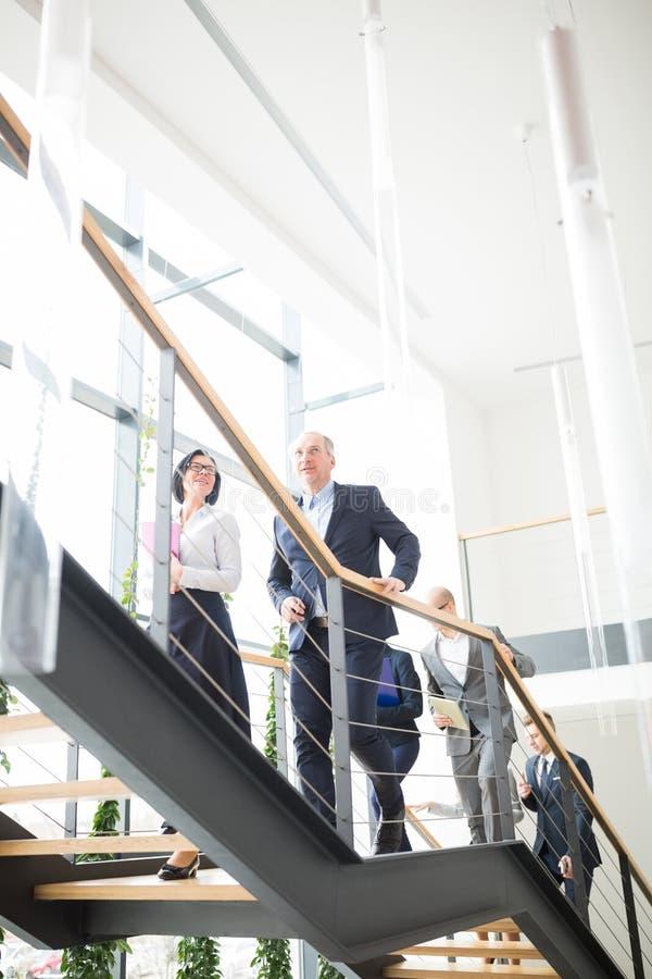 Hommes d'affaires montant des escaliers dans le bureau moderne photos libres de droits