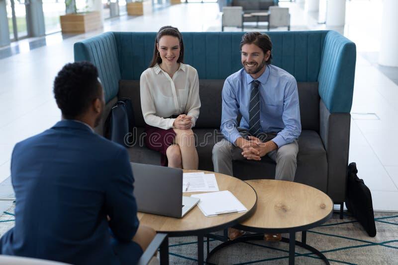 Hommes d'affaires multi-ehnic agissant l'un sur l'autre les uns avec les autres dans le lobby image stock