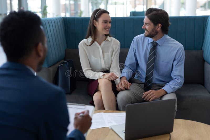 Hommes d'affaires multi-ethniques agissant l'un sur l'autre les uns avec les autres dans le lobby photos stock