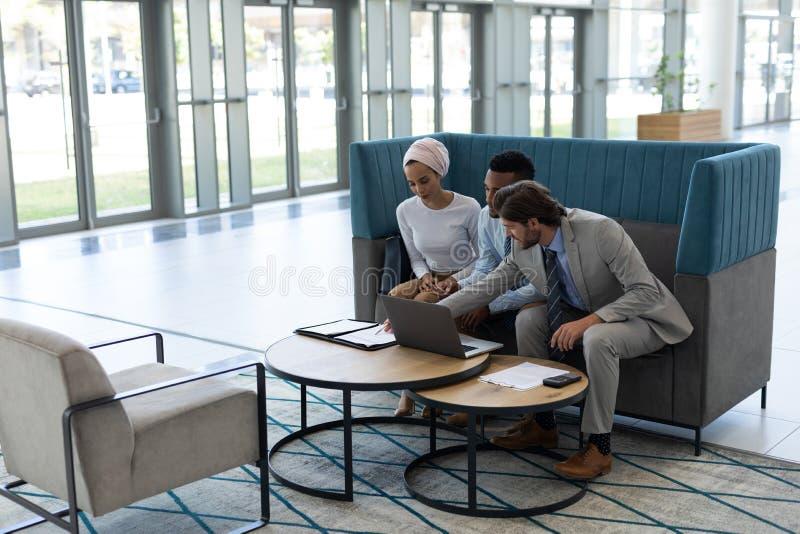 Hommes d'affaires multi-ethniques discutant au-dessus de l'ordinateur portable dans le lobby photo stock