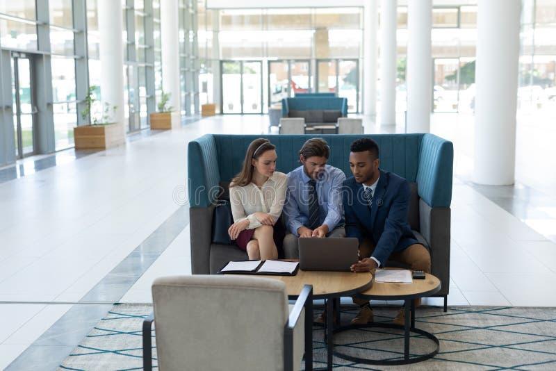Hommes d'affaires multi-ethniques discutant au-dessus de l'ordinateur portable dans le lobby images stock