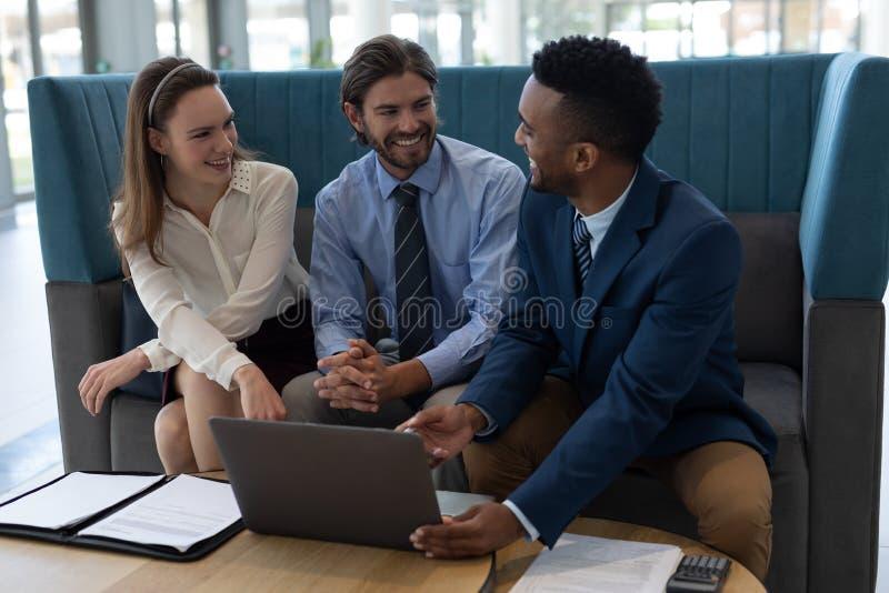 Hommes d'affaires multi-ethniques discutant au-dessus de l'ordinateur portable dans le lobby photos stock