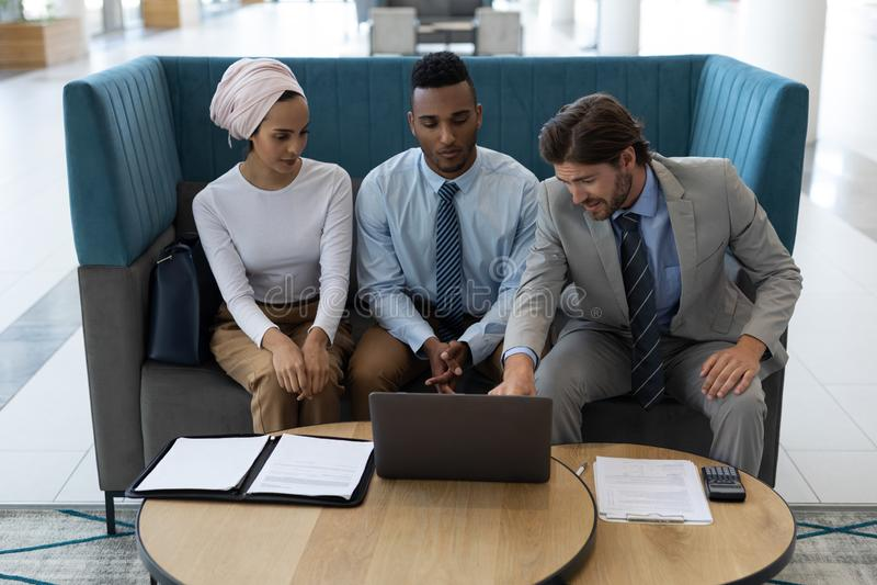 Hommes d'affaires multi-ethniques discutant au-dessus de l'ordinateur portable dans le lobby image stock