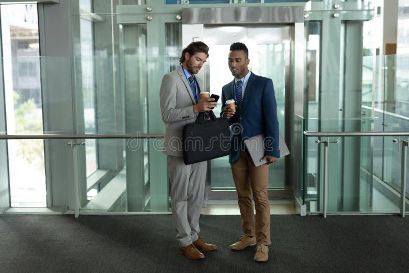 Hommes d'affaires multi-ethniques discutant au-dessus du téléphone portable près de l'ascenseur photo libre de droits