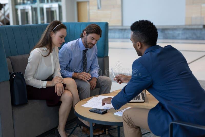 Hommes d'affaires multi-ethniques regardant les papiers de contrat dans le lobby image libre de droits