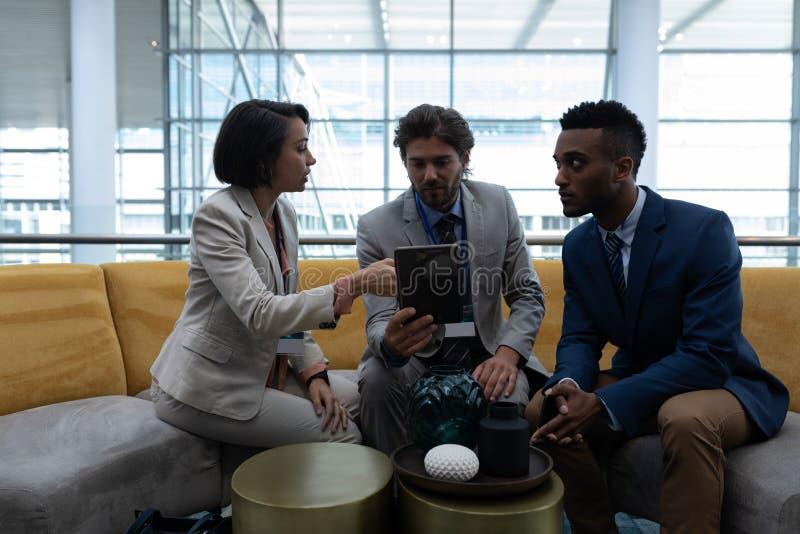 Hommes d'affaires multi-ethniques s'asseyant et discutant au-dessus du comprimé numérique dans le lobby au bureau photo libre de droits