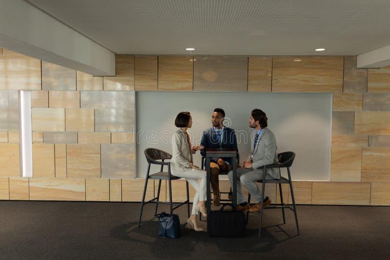 Hommes d'affaires multi-ethniques s'asseyant et discutant les uns avec les autres dans le lieu de réunion photo stock