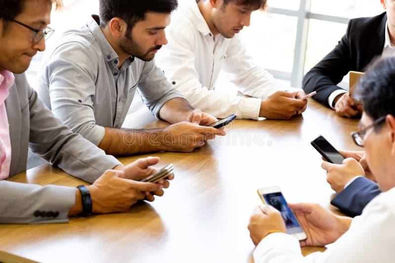Hommes d'affaires multi-ethniques tous utilisant des téléphones sur le bureau photos libres de droits