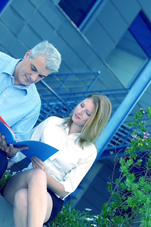 Hommes d'affaires observant un fichier en dehors de teinte bleue images libres de droits