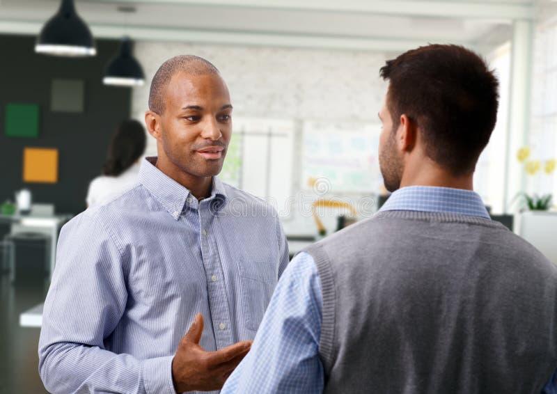 Hommes d'affaires occasionnels parlant au bureau photo stock