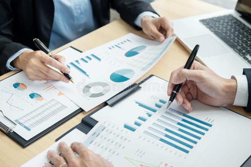 Hommes d'affaires parlant la discussion avec la planification de collègue analysant les diagrammes et les graphiques financiers d photographie stock libre de droits