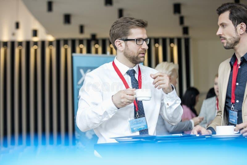 Hommes d'affaires parlant pendant la pause-café au lobby du centre de congrès photos libres de droits
