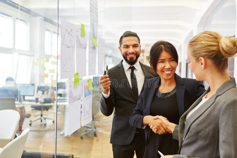 Hommes d'affaires partageant la poignée de main dans le bureau images libres de droits