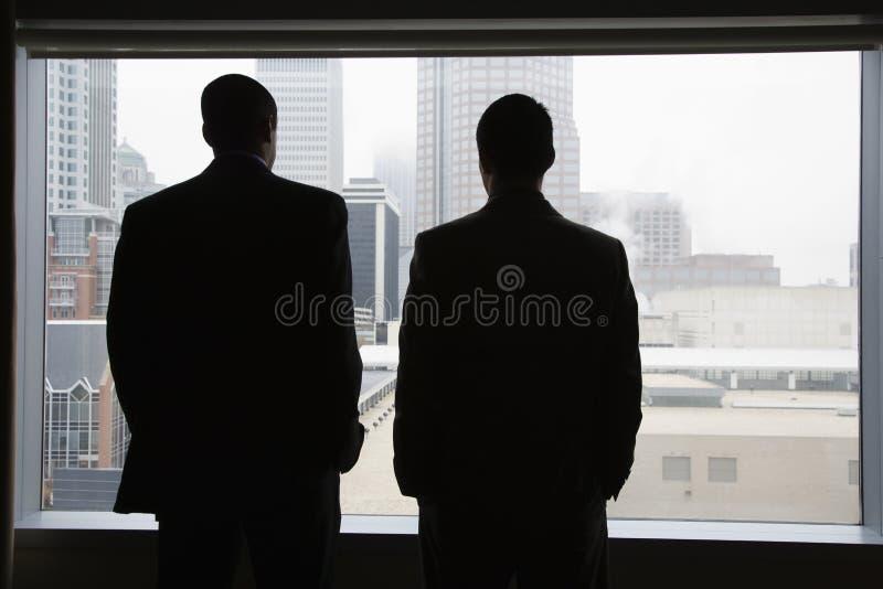 Hommes d'affaires regardant hors d'un hublot image libre de droits