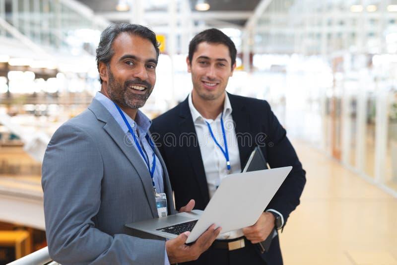 Hommes d'affaires regardant la caméra tout en travaillant sur l'ordinateur portable dans un bureau moderne images stock