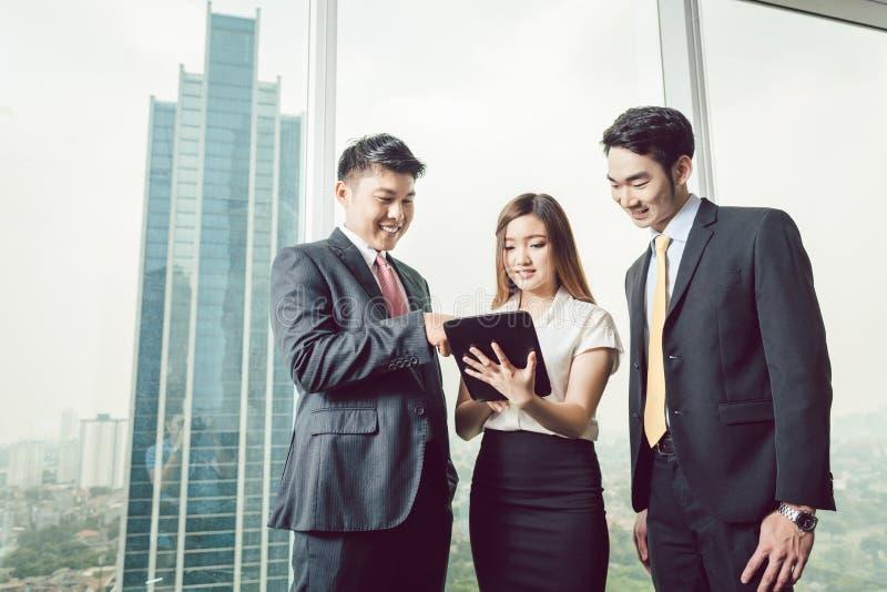 Hommes d'affaires regardant le comprimé numérique photo stock