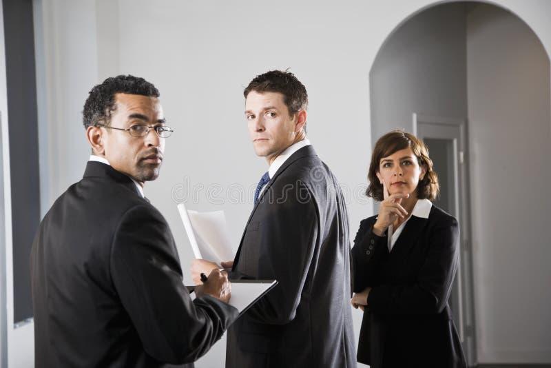 Hommes d'affaires sérieux regardant au-dessus de l'épaule photos libres de droits