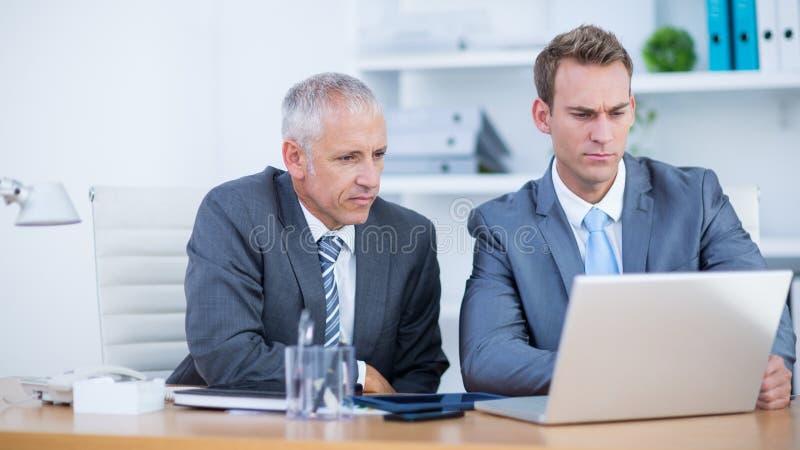 Download Hommes D'affaires Sérieux Travaillant Ensemble Sur L'ordinateur Portable Image stock - Image du businessmen, discuter: 56483027