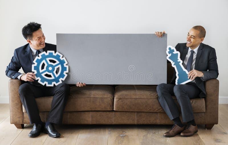 Hommes d'affaires s'asseyant ainsi que des icônes images libres de droits