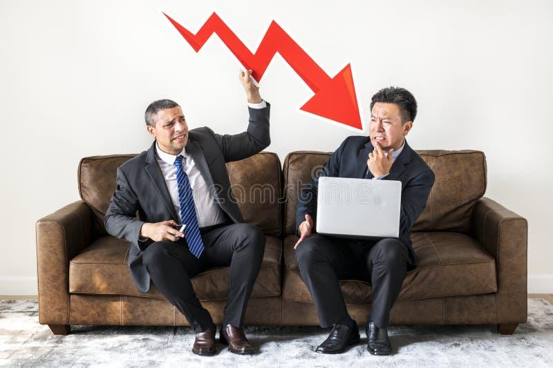Hommes d'affaires s'asseyant ainsi que des icônes images stock
