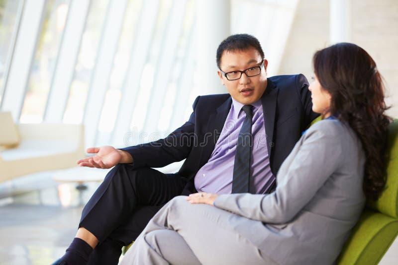 Hommes d'affaires s'asseyant sur le sofa dans le bureau moderne photo stock