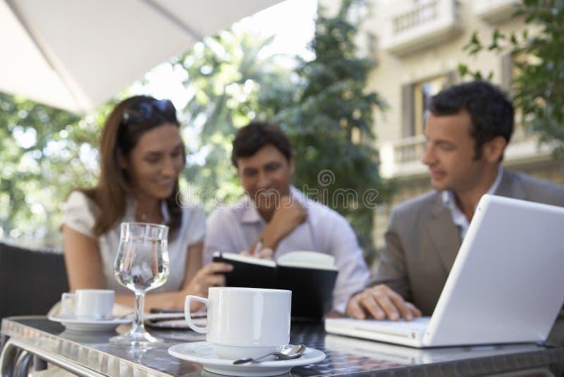 Hommes d'affaires se réunissant au café extérieur photo stock