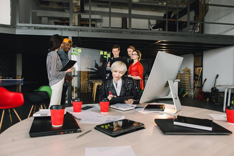 Hommes d'affaires se réunissant aux idées de bureau et de part sur le mur de verre Concept de s?ance de r?flexion Jeune femme dan image stock