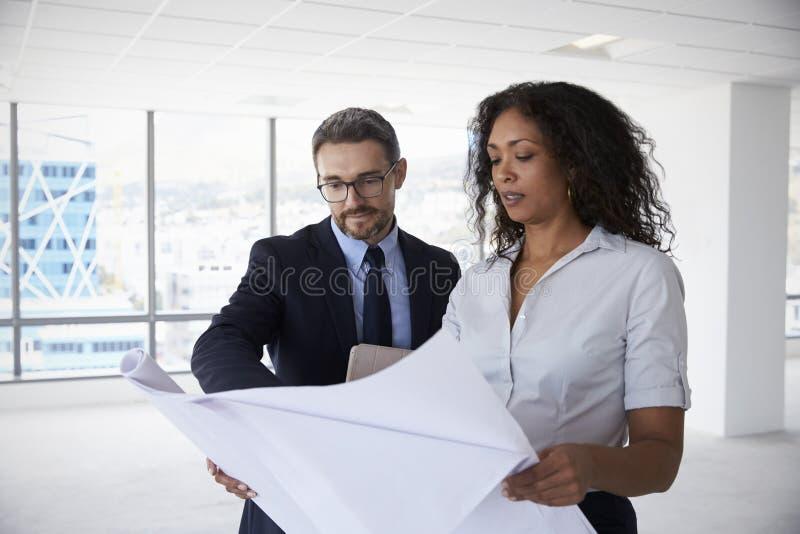 Hommes d'affaires se réunissant pour regarder des plans dans le bureau vide images stock