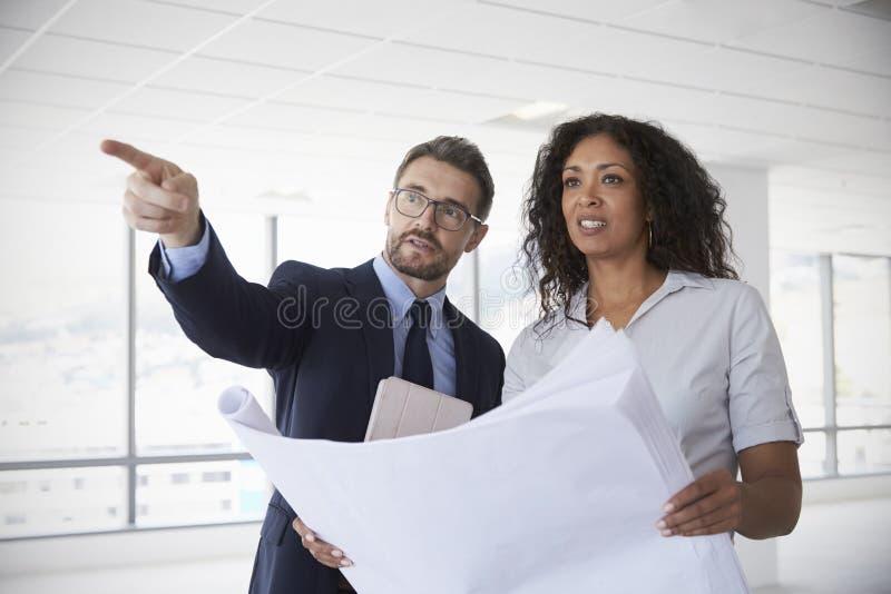 Hommes d'affaires se réunissant pour regarder des plans dans le bureau vide photo libre de droits